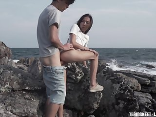 Young couple is making love primarily the rocky shore